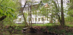 """Das Freizeitheim """"Grabentour"""" hinter Bäumen sichtbar. Fluss im Vordergrund."""